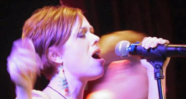 Amber Pennington singing into microphone